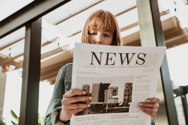 Mujer leyendo un periódico en un café