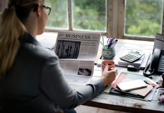Mujer leyendo el periódico y tomando café