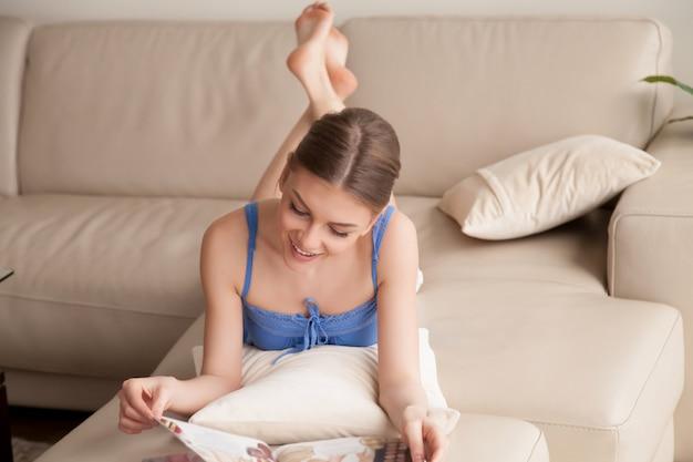 Mujer leyendo revista de papel mientras descansa en casa