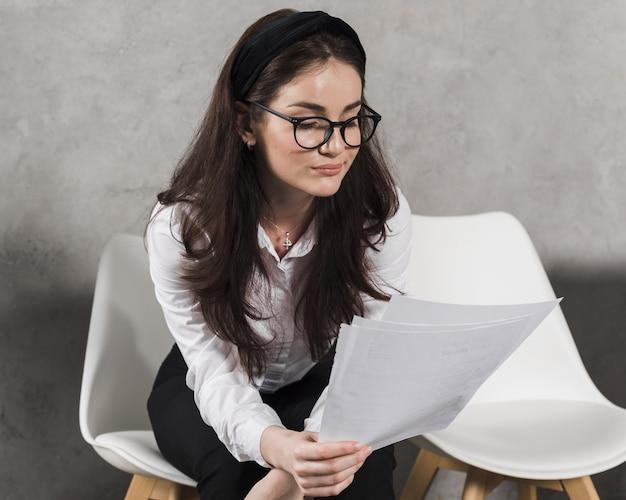 Mujer leyendo su currículum antes de asistir a una entrevista de trabajo