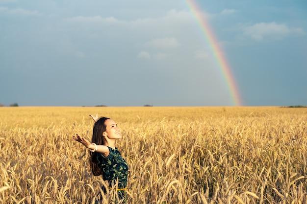 Mujer libre en un campo con espigas doradas con las manos abiertas mirando la puesta de sol sobre un fondo de arco iris