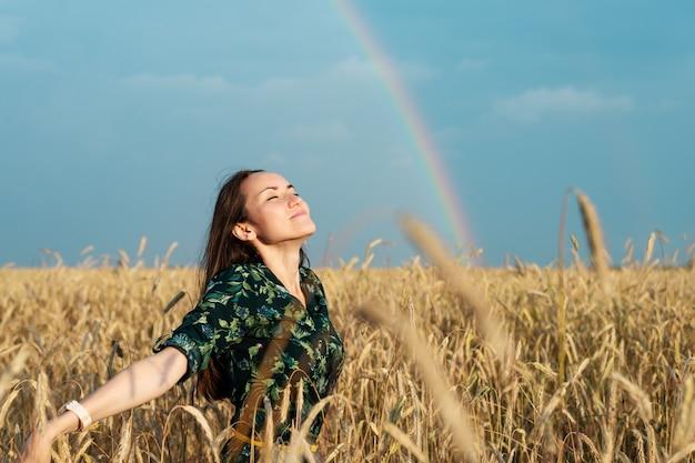 Una mujer libre en un campo de trigo con las manos abiertas respira aire contra el fondo de un arco iris, libertad, ecología