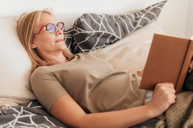Mujer con libro de lectura de máscara médica en cuarentena en casa