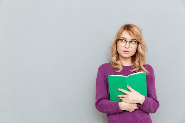 Mujer con libro pensando