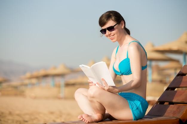 Mujer con libro en la playa