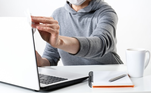 Mujer limpia una computadora con una toallita antibacteriana