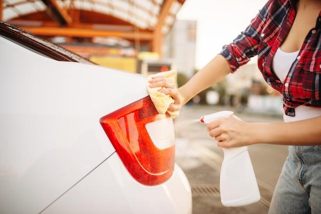 Mujer limpia las luces traseras del coche con spray