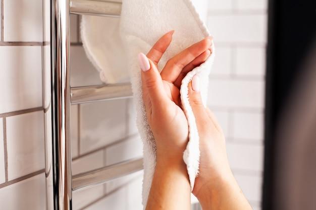 Mujer se limpia las manos con una toalla en un baño luminoso