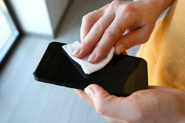 La mujer limpia la pantalla de su teléfono con un tejido antibacteriano húmedo.