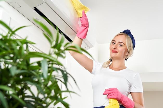 Mujer limpiando el aire acondicionado con un trapo. servicio de limpieza o concepto de ama de casa