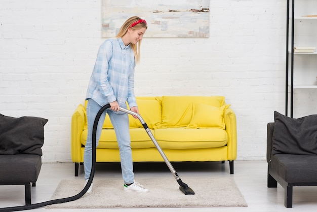 Mujer limpiando la alfombra con aspiradora