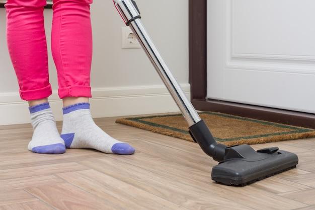 Mujer está limpiando con aspiradora