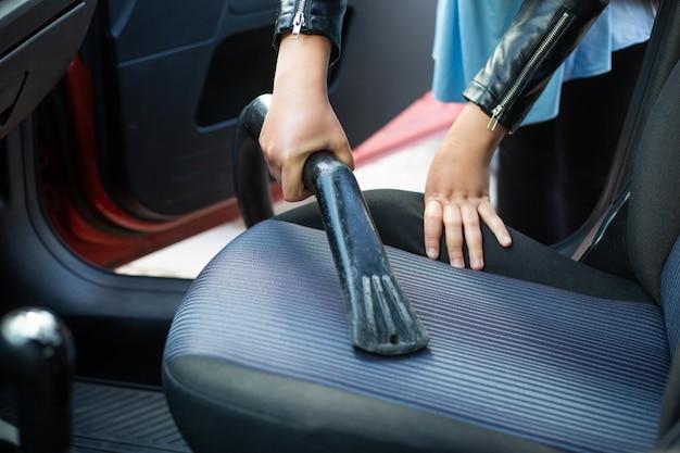 Mujer limpiando, aspirando el interior del coche con una aspiradora, concepto de transporte
