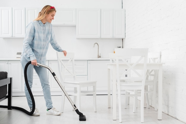 Mujer limpiando la casa con aspiradora