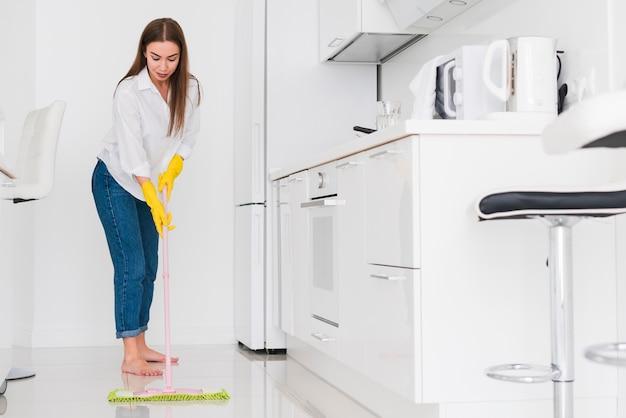 Mujer limpiando la cocina con una fregona vista larga