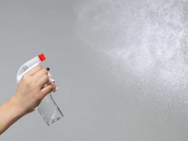 Mujer limpiando la habitación con spray
