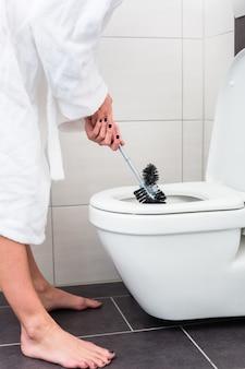 Mujer limpiando el inodoro con cepillo de baño