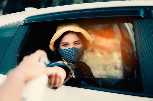 Mujer limpiando una mano con gel de alcohol al 75% antes de conducir a través del examen para prevenir coronavirus o covid-19