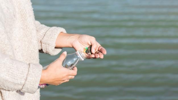 Mujer limpiando mar de botella de plástico