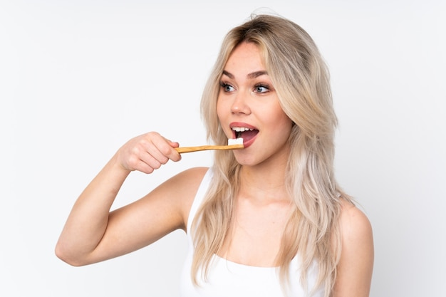 Mujer limpiando sus dientes sobre pared aislada
