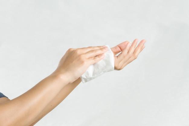 Mujer limpiando sus manos con papel de seda blanco suave. aislado en un fondo blanco