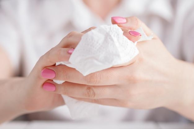 Mujer limpiando sus manos con papel de seda blanco.