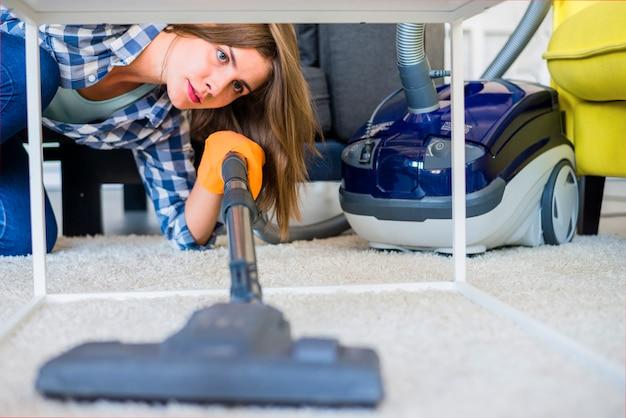 Mujer de limpieza de alfombras con aspiradora.