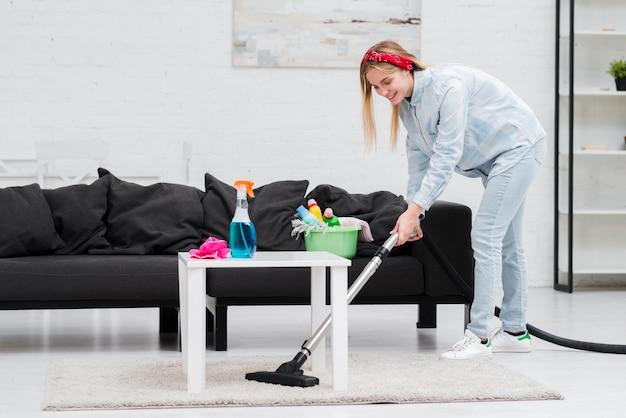 Mujer de limpieza con aspiradora