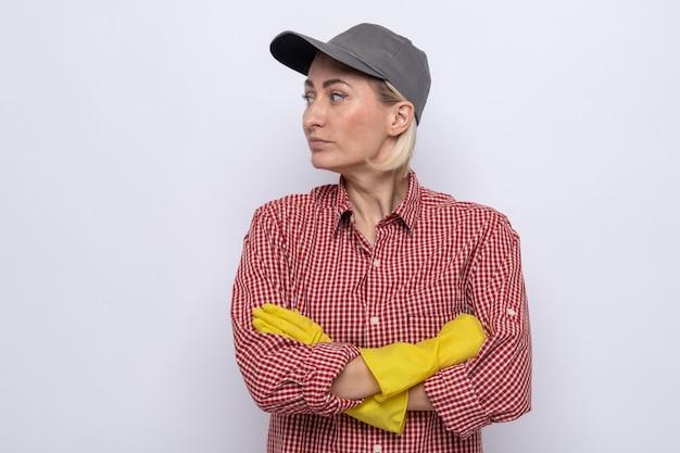Mujer de la limpieza en camisa a cuadros y gorra con guantes de goma mirando a un lado con cara seria con los brazos cruzados de pie sobre fondo blanco.