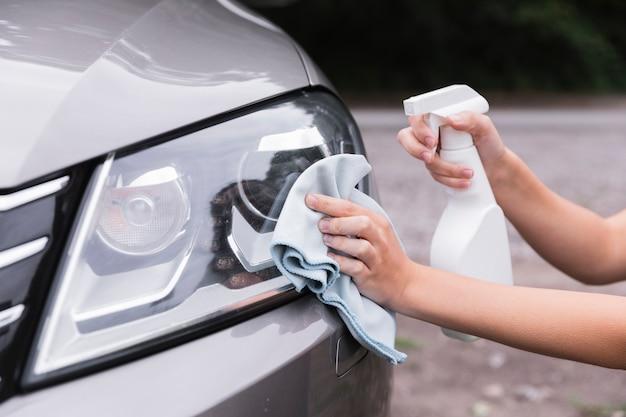 Mujer, limpieza, faros del coche