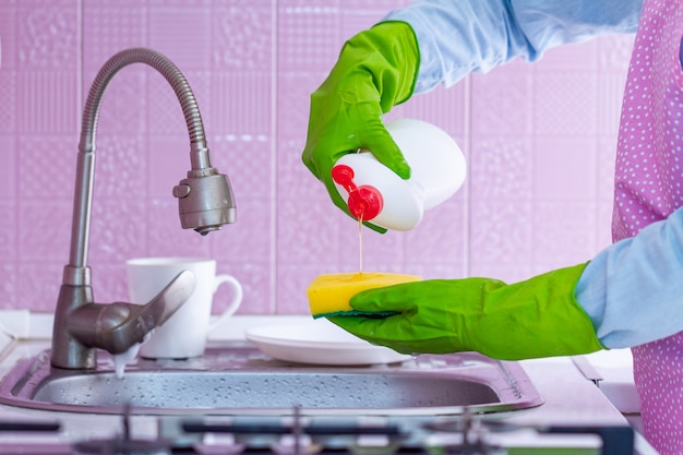 Mujer de la limpieza con guantes de goma verde y delantal con esponja y detergente para lavar los platos en la cocina en casa
