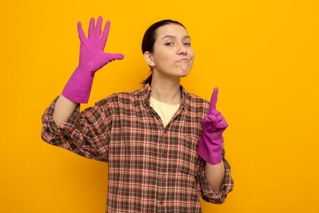 Mujer de limpieza joven en camisa a cuadros en guantes de goma con sonrisa de confianza en la cara que muestra el número seis con los dedos de pie en naranja