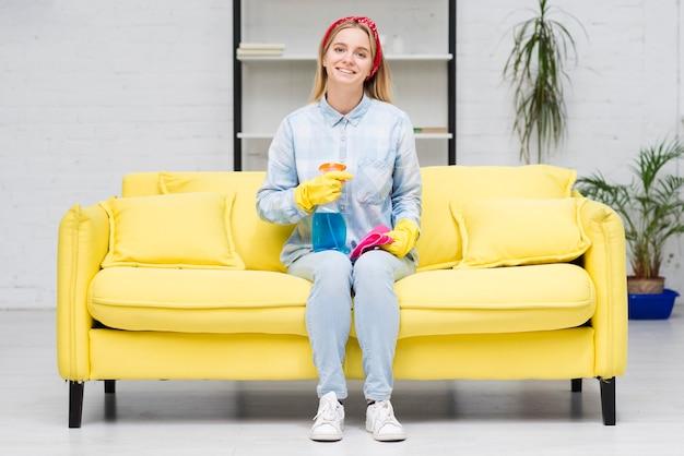 Mujer de limpieza sentada en el sofá