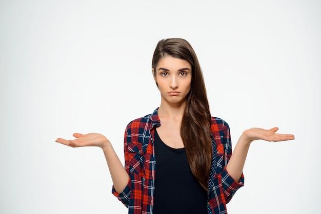 Mujer linda confundida encogerse de hombros con las manos extendidas
