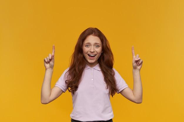 Mujer linda y feliz con el pelo largo de jengibre. vistiendo camiseta rosa. concepto de emoción. sonriendo ampliamente, señalando con el dedo índice el espacio de la copia. aislado sobre pared naranja