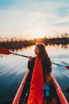 Mujer linda feliz que sostiene la paleta en un kayak en el río