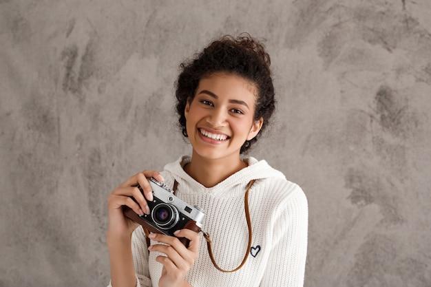 Mujer linda inconformista tomando fotos en cámara retro