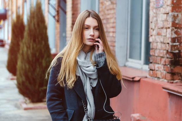 La mujer linda joven que camina en la calle utiliza un teléfono elegante.
