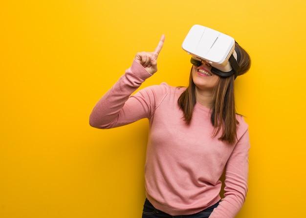 Mujer linda joven que lleva una realidad virtual gafas que muestran el número uno
