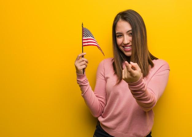Mujer linda joven que sostiene una bandera de estados unidos invitando a venir