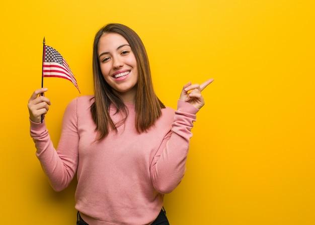 Mujer linda joven que sostiene una bandera de estados unidos que señala al lado con el dedo