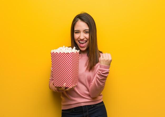 Mujer linda joven que sostiene un cubo de las palomitas de maíz sorprendido y chocado