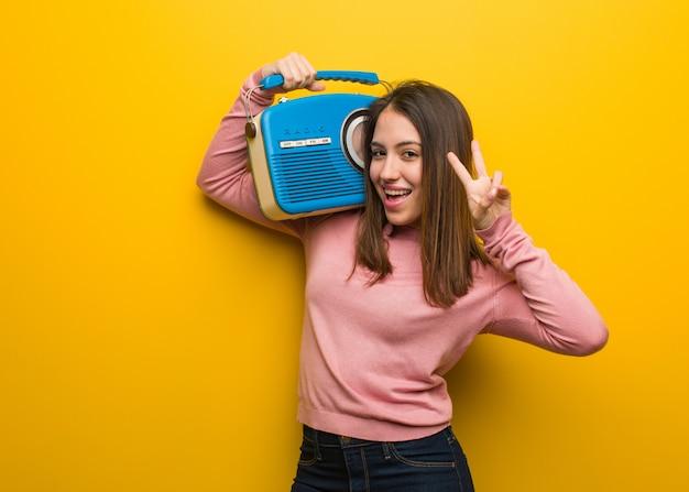 Mujer linda joven que sostiene una diversión de radio vintage y feliz haciendo un gesto de victoria