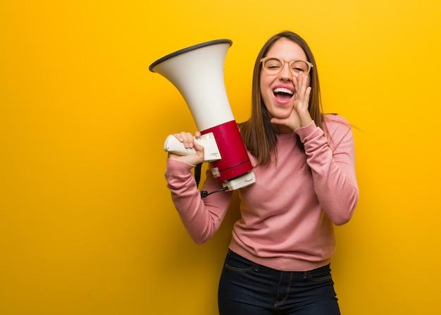 Mujer linda joven que sostiene un megáfono que grita algo feliz al frente