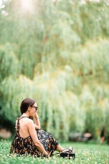 La mujer linda está leyendo el mensaje de texto en el teléfono móvil mientras que se sienta en el parque.
