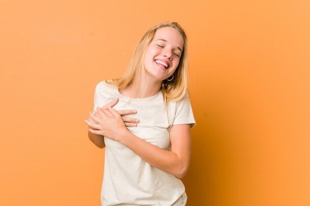 Mujer linda y natural del adolescente que ríe manteniendo las manos en el corazón, concepto de felicidad.