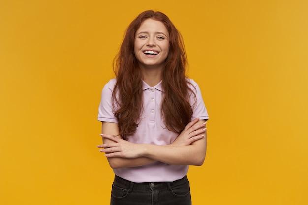 Mujer linda y positiva con el pelo largo de jengibre. vistiendo camiseta rosa. concepto de personas y emociones. sostiene los brazos cruzados y sonríe ampliamente. aislado sobre pared naranja