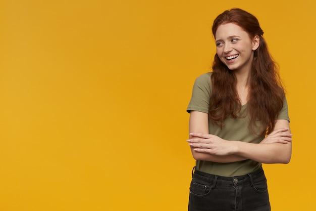 Mujer linda y positiva con el pelo largo de jengibre. vistiendo camiseta verde. concepto de personas y emociones. sosteniendo los brazos cruzados y sonriendo. mirando a la izquierda en el espacio de la copia, aislado sobre una pared naranja