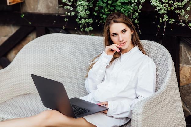 Mujer linda que hace compras en línea por la computadora portátil en el tiempo de mañana.