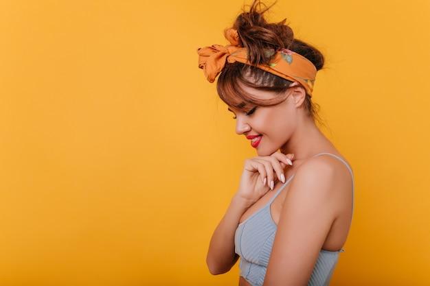 Mujer linda tímida con traje retro posando con sonrisa en el espacio amarillo